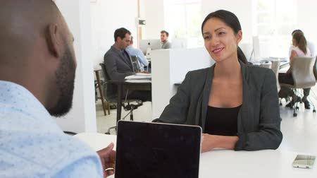 over the shoulder view : Asian woman greeting a man at a meeting in a busy office Stock Footage