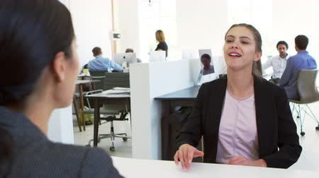 over the shoulder view : Two women sitting at an interview in an open plan office Stock Footage