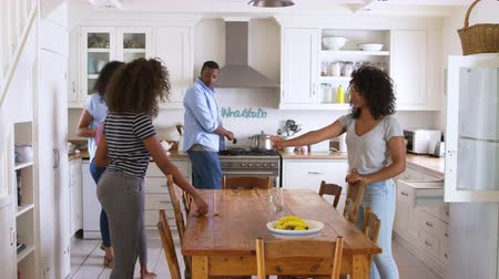 afro americana : Family With Teenage Children Laying Table For Meal In Kitchen