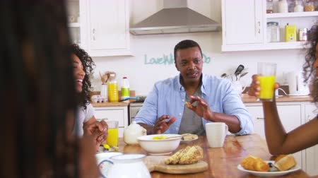 afro americana : Family With Teenage Children Eating Breakfast In Kitchen