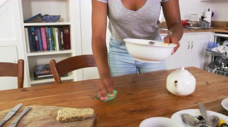 clearing the table : Teenage Girl Wiping Down Breakfast Table In Kitchen After Meal Stock Footage
