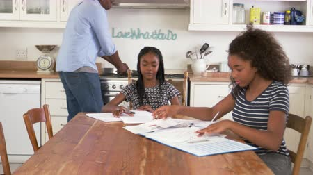 encouraging : Father Helping Two Daughters Sitting At Table Doing Homework Stock Footage