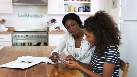 encouraging : Mother Helps Teenage Daughter With Homework Using Digital Tablet