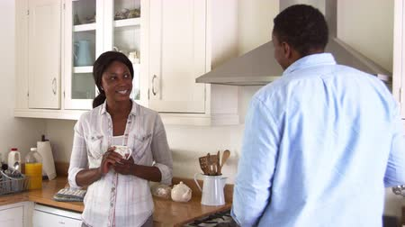 drinking coffee : Mature Couple Chat In Kitchen As Man Prepares Meal In Kitchen Stock Footage