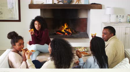 aberto : Family Sitting On Sofa In Lounge Next To Open Fire Eating Pizza Stock Footage