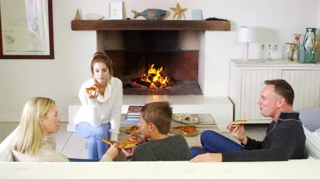 közepes : Family Sitting On Sofa In Lounge Next To Open Fire Eating Pizza Stock mozgókép