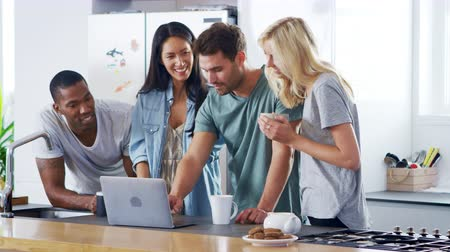 socializing : Friends Looking At Laptop And Drinking Coffee In Modern Kitchen