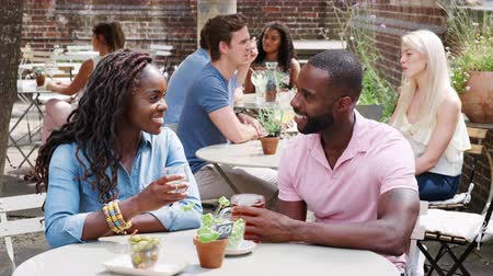 socializing : Young couple meeting for drinks in outdoor bar - shot in slow motion