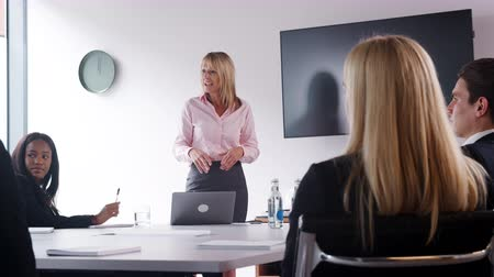 internar : Mature businesswoman addressing candidates on graduate recruitment day in boardroom - shot in slow motion