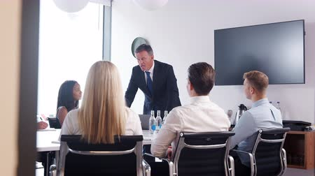 recrutamento : Mature businessman addressing candidates on graduate recruitment day in boardroom - shot in slow motion