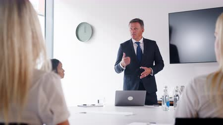 elliler : Mature businessman addressing candidates on graduate recruitment day in boardroom - shot in slow motion