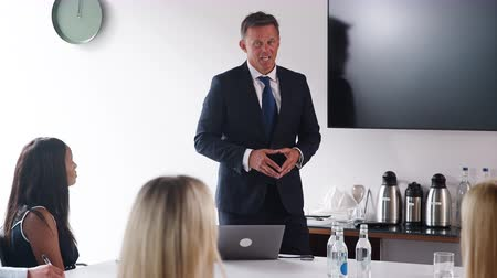 elliler : Camera tracks across frame to show mature businessman addressing candidates on graduate recruitment day in boardroom - shot in slow motion