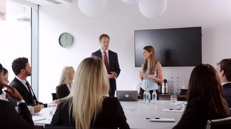 internar : Young businessman and businesswoman addressing candidates on graduate recruitment day in boardroom Stock Footage