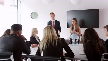 recruitment process : Young businessman and businesswoman addressing candidates on graduate recruitment day in boardroom Stock Footage