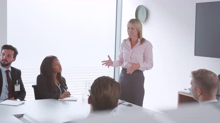 entry level : Mature businesswoman addressing candidates on graduate recruitment day in boardroom - shot in slow motion