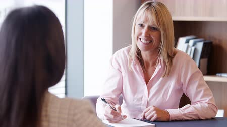 internar : Mature businesswoman interviewing female candidate in office on graduate recruitment day