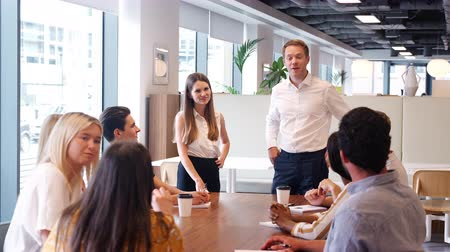 recruitment process : Young businessman and businesswoman addressing group meeting around table in modern office at graduate recruitment assessment day - shot in slow motion Stock Footage