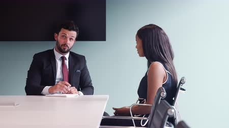 recruitment process : Businessman interviewing female candidate at boardroom table on graduate recruitment day Stock Footage