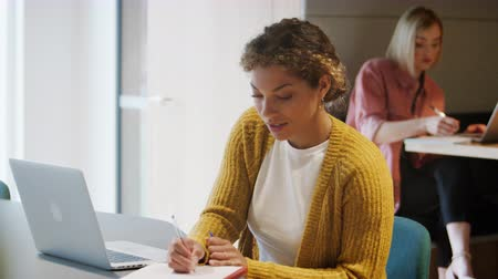 artistiek : Smiling young adult woman working at a laptop computer in a creative office, her colleague working the background