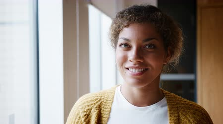 raam : Young mixed race millennial woman standing by the window in an office turns to camera and smiles, head and shoulders, close up