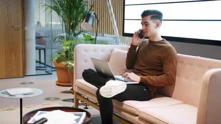 vista lateral : Young white businessman using phone working on a laptop computer sitting on a sofa in a casual office Stock Footage