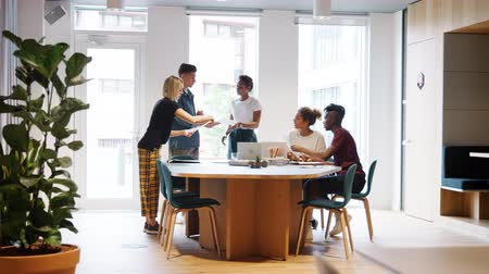 dokumentum : Creative millennial team doing paperwork together standing and sitting around a table in a large office, full length view Stock mozgókép