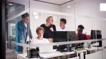 arme verschränkt : Creative business team gathered around a laptop computer in a small office cubicle, seen through glass Videos