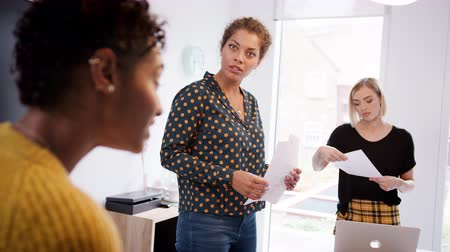 artistiek : Three female creatives in discussion over paperwork during a casual meeting in an office meeting room, selective focus