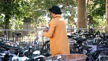 dojíždění : Young black woman wearing yellow unbuttoned yellow pea coat, black hat and sunglasses parking her bicycle, putting on crossbody handbag and and walking away, out of shot, smiling, side view