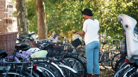 dojíždění : Young black woman wearing white t shirt, blue jeans and sunglasses parking her bicycle, putting on crossbody handbag and walking away smiling, handheld Dostupné videozáznamy