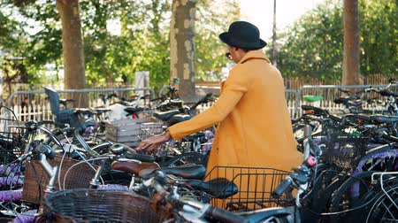 trzy : Young woman wearing unbuttoned yellow pea coat, black hat and sunglasses parking her bicycle, putting on crossbody bag and walking away smiling, side view, tracking shot