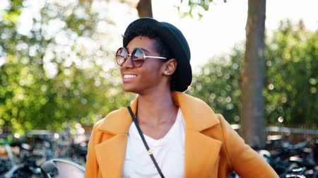 ajustando : Fashionable young black woman standing outdoors wearing sunglasses, a yellow coat and a black hat looking to camera and laughing, close up, focus on foreground