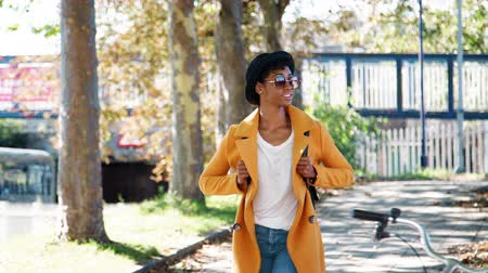 trzy : Fashionable young black woman wearing a hat, sunglasses, blue jeans and a yellow pea coat walking along a treelined city street on a sunny day, looking around, smiling, front view