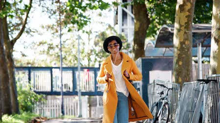 wearing earphones : Fashionable young black woman wearing a hat, sunglasses, blue jeans and a yellow pea coat walking along a treelined street towards camera, listening to music with earphones and looking around, backlit, low angle