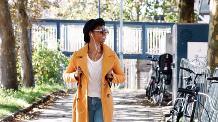 wearing earphones : Fashionable young black woman wearing a hat, sunglasses, an unbuttoned yellow pea coat and jeans, walking along a treelined city street listening to music
