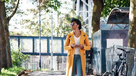 wearing earphones : Fashionable young black woman wearing a hat, sunglasses, an unbuttoned yellow pea coat and jeans walking along a treelined street looking around and using smartphone, low angle Stock Footage