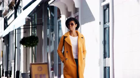 szelektív összpontosít : Fashionable young black woman wearing blue jeans and an unbuttoned yellow pea coat walking in the street past shops on a sunny day, smiling, close up Stock mozgókép