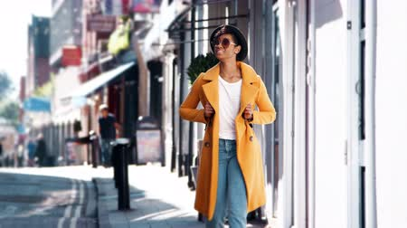 kısa : Fashionable young black woman wearing blue jeans and an unbuttoned yellow pea coat walking on pavement near shops on a sunny day smiling, close up