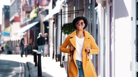 trzy : Fashionable young black woman wearing blue jeans and an unbuttoned yellow pea coat walking on a street past shops on a sunny day, smiling, close up