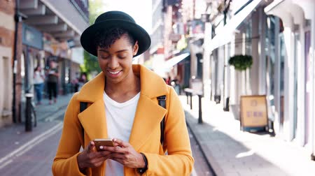 vie urbaine : Millennial black woman wearing a yellow pea coat and a homburg hat using her smartphone, standing in the street on a sunny day, close up
