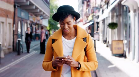 šik : Millennial black woman wearing a yellow pea coat and a homburg hat using her smartphone standing on a street and walking out of shot, close up