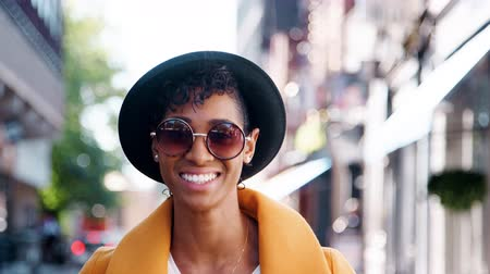 focus on foreground : Millennial black woman wearing a yellow pea coat, sunglasses and a homburg hat, standing on a city street smiling to camera, close up