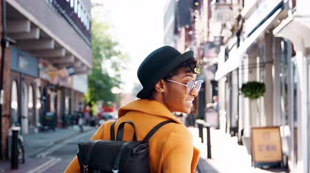 arka görünüm : Back view of fashionable young black woman wearing a hat and a yellow pea coat walking in the street and turning to look back to camera Stok Video