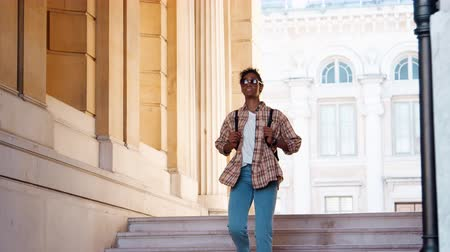 wearing earphones : Young black woman wearing a plaid shirt and blue jeans walking down street stairs at the entrance of a historical building, full length Stock Footage