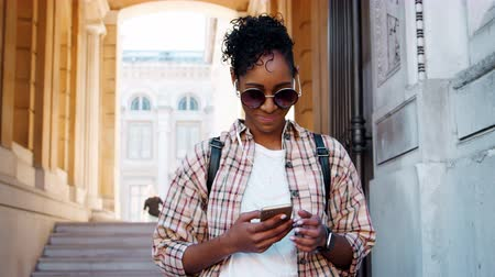 wearing earphones : Young adult woman wearing a plaid shirt standing in front of a historical building entrance using her smartphone