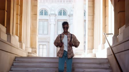 trzy : Front view of young black woman wearing sunglasses, blue jeans and a plaid shirt walking down steps outside a historical building looking around and listening to music with earphones, low angle
