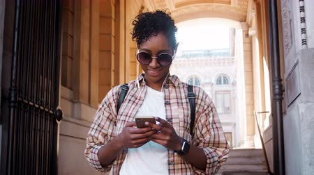 historical : Close up of fashionable young black woman wearing sunglasses and plaid shirt using her smartphone standing outside the entrance of a historical building, low angle