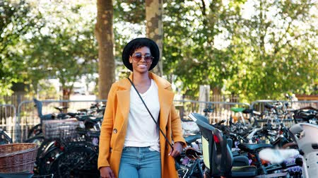 etnia africano : Fashionable young black woman wearing a hat, sunglasses, blue jeans, an unbuttoned yellow pea coat and a crossbody handbag walking amongst parked bicycles, smiling to camera