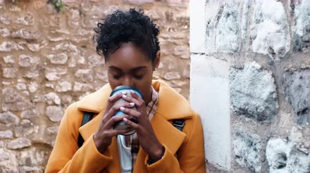 плед : Millennial black woman wearing a yellow coat leaning on a stone wall in an alleyway drinking a takeaway coffee, close up