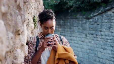 плед : Millennial woman with short curly hair wearing plaid shirt leaning on stone wall in the street drinking a takeaway coffee, close up Стоковые видеозаписи